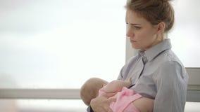 La madre cansada que celebra al bebé en las manos acerca a la ventana Mujer cansada que detiene al niño metrajes