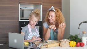 La madre cariñosa feliz ayuda a su hija con el hallazgo una nueva receta que cuece metrajes