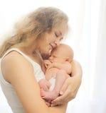 La madre cariñosa joven celebra blando en niño durmiente de las manos Imágenes de archivo libres de regalías