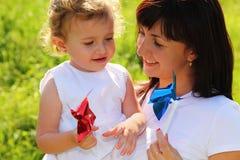La madre celebra a la niña con el pinwheel Fotos de archivo libres de regalías
