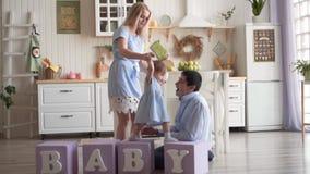 La madre celebra las manos y las ventajas de su hija en los cubos, mientras que el papá se sienta al lado de él en el piso metrajes