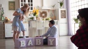 La madre celebra las manos y las ventajas de su hija en los cubos, mientras que el pap? se sienta al lado de ?l en el piso almacen de video