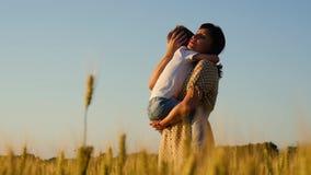 La madre celebra a su hijo en sus brazos contra el cielo azul en un campo de trigo en la puesta del sol Una madre que abraza un r almacen de video