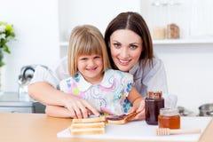La madre che aiuta la sua figlia prepara la prima colazione Fotografie Stock Libere da Diritti