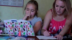 La madre che aiuta sua figlia fa il compito La ragazza fa le lezioni, lettura, scrittura stock footage