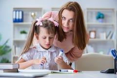 La madre che aiuta sua figlia a fare compito Immagini Stock