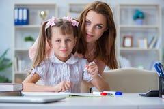 La madre che aiuta sua figlia a fare compito Fotografia Stock