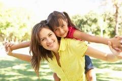 La madre che dà il giro della figlia sopra appoggia in sosta Immagine Stock