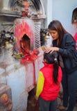 La madre che dipinge un piccolo punto rosso ha chiamato il tika sulla fronte del suo bambino allo stupa di Boudhanath, Kathmandu, immagini stock libere da diritti