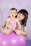 La madre con la bambina sulla grande palla Immagine Stock