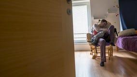 La madre che riposa su una sedia di oscillazione come suo bambino dorme nel suo rivestimento Fotografie Stock