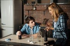 La madre chocada cogió a su hijo mientras que bebía la cerveza Imágenes de archivo libres de regalías