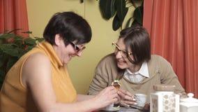 La madre come la torta y su café de consumición de la hija Cocina, risa, conversación Mujeres con los vidrios metrajes