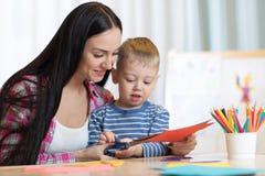 La madre con la diversión del niño pequeño cortó el papel coloreado de las tijeras imagenes de archivo