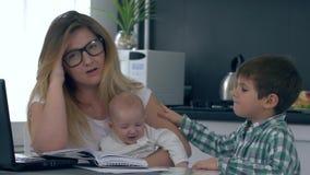 La madre con dolores de cabeza cansó de trabajo y los niños, mujer toman la cabeza en manos y la mirada en la cámara almacen de video