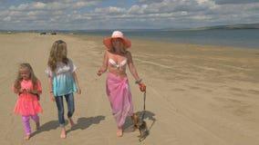 La madre con dos hijas está caminando a lo largo de la playa almacen de metraje de vídeo