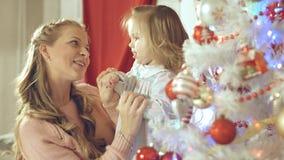 La madre con el bebé adorable que se divierte y se besa en el árbol de navidad en casa Fotos de archivo
