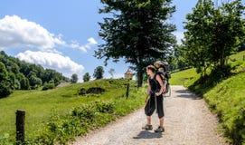 La madre con el bebé en portador de la mochila está caminando en montañas Foto de archivo libre de regalías
