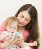 La madre con el bebé está considerando un juguete. Imágenes de archivo libres de regalías