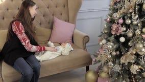 La madre con el bebé recién nacido se sienta cerca del árbol de navidad metrajes