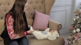 La madre con el bebé recién nacido se sienta cerca del árbol de navidad almacen de metraje de vídeo