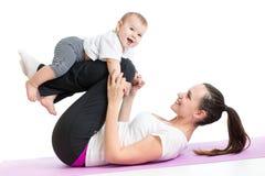 La madre con el bebé hace ejercicios de la gimnasia y de la aptitud Foto de archivo libre de regalías