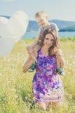 La madre con el hijo se está divirtiendo en campo de la manzanilla Fotos de archivo libres de regalías