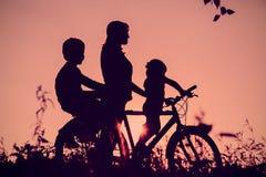 La madre con el montar a caballo del hijo y de la hija bike en la puesta del sol Imágenes de archivo libres de regalías