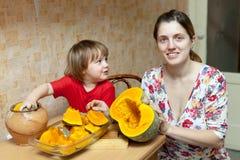 La madre con el niño cocina la calabaza Imagen de archivo