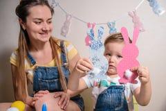 La madre con el niño creativo que se divierte mide el tiempo junta fotos de archivo libres de regalías