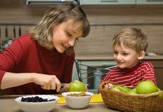 La madre con el niño es fruta comida Foto de archivo libre de regalías