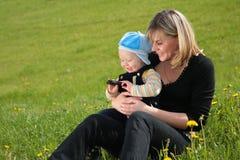 La madre con el niño se sienta en hierba Fotos de archivo