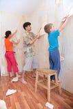 La madre con el padre y el hijo rompen los papeles pintados de Fotografía de archivo