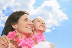 La madre con es hija que tiene un collar rosado Foto de archivo