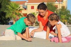 La madre con i bambini si siede sulla spiaggia e sul tiraggio immagine stock libera da diritti