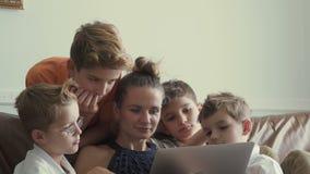La madre con i quattro figli guarda il film sul computer portatile a casa archivi video