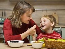 La madre con il bambino è frutta alimentare in cucina Immagine Stock