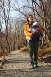 La madre con il bambino in imbracatura del marsupio cammina dalla foresta roa fotografie stock