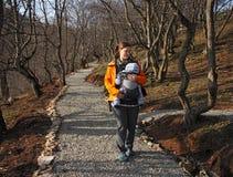 La madre con il bambino in marsupio cammina dal sentiero forestale immagine stock