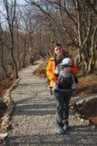 La madre con il bambino in marsupio cammina dalla strada della ghiaia della foresta fotografia stock libera da diritti