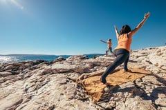 La madre con il figlio espone al sole l'esercizio di mattina di yoga di saluto sulla s Immagini Stock
