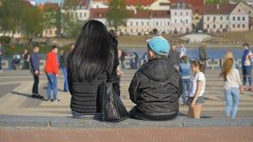 La madre con il figlio si rilassa nella città e guarda i giochi di sport - slowmo 180 fps archivi video