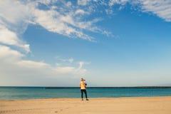 La madre con il neonato gode dell'alba su una spiaggia Immagine Stock Libera da Diritti