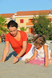 La madre con la figlia si siede sulla spiaggia e dissipa sulla sabbia fotografie stock