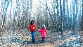 La madre con la figlia sta camminando attraverso la foresta della molla nei raggi soleggiati video d archivio