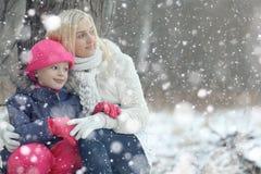 La madre con la hija camina en el bosque del invierno imagen de archivo libre de regalías