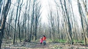 La madre con la hija está caminando a través del bosque de la primavera en rayos soleados metrajes