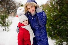 La madre con la hija ha construido un muñeco de nieve y disfruta Foto de archivo