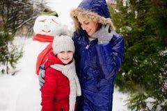 La madre con la hija ha construido un muñeco de nieve y disfruta Imágenes de archivo libres de regalías