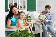 La madre con la hija y el padre con el hijo se sientan en la tabla blanca Imágenes de archivo libres de regalías